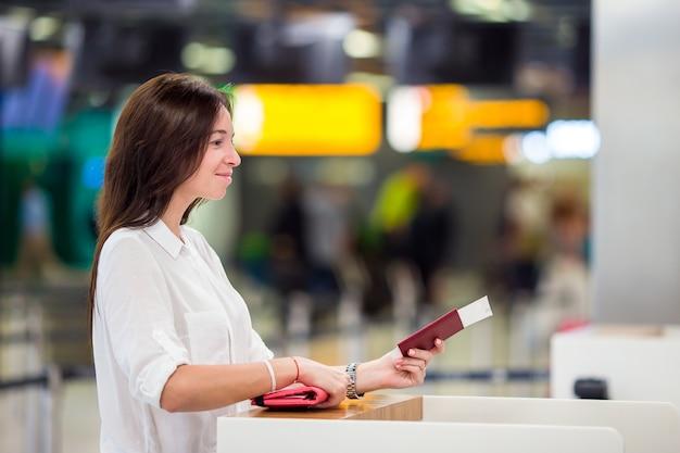 Gelukkige vrouw die met kaartjes en paspoorten bij luchthaven op het inschepen wachten
