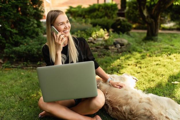 Gelukkige vrouw die met laptop werkt en met hond labrador in groen park speelt