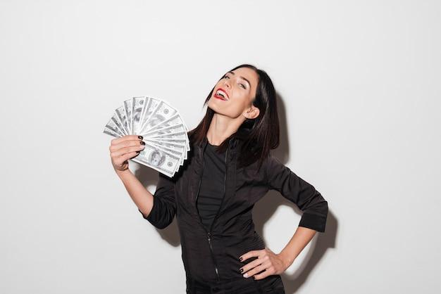 Gelukkige vrouw die met rode lippen geld houden.