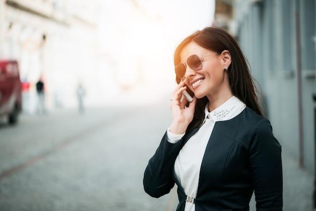 Gelukkige vrouw die met zonglazen helder terwijl het spreken op telefoon glimlachen