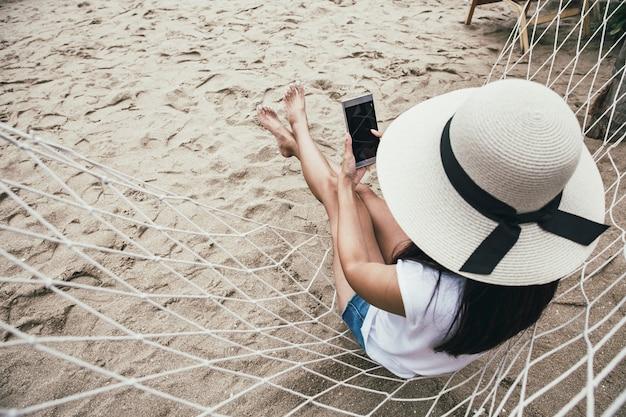 Gelukkige vrouw die mobiele telefoon in hangmat met behulp van