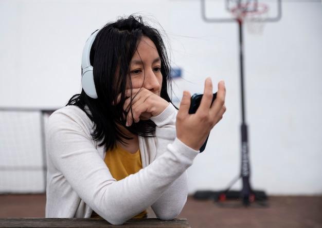 Gelukkige vrouw die muziek luistert op straat