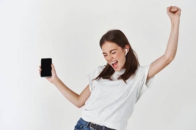Gelukkige vrouw die naar muziek luistert in een draadloze koptelefoon en een smartphone vasthoudt, danst en zingt over een witte muur