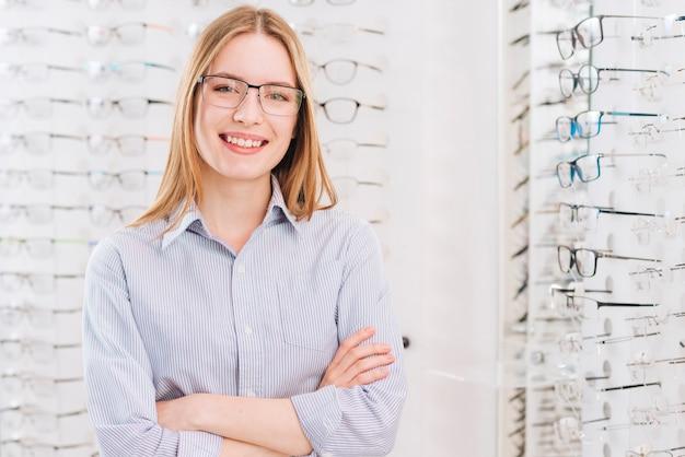 Gelukkige vrouw die nieuwe glazen zoekt bij optometrist