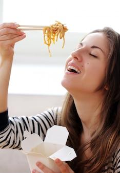 Gelukkige vrouw die noedels eet