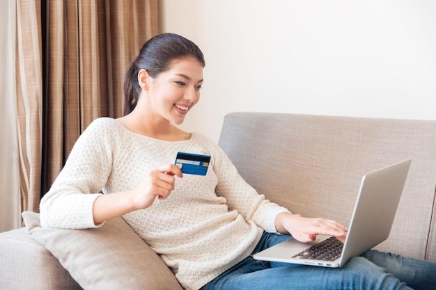 Gelukkige vrouw die online op laptopcomputer met creditcard thuis koopt