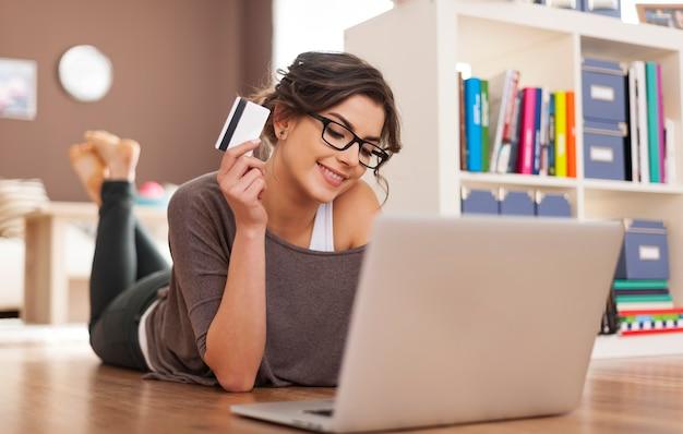 Gelukkige vrouw die online thuis winkelt