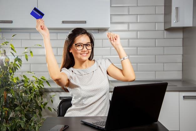 Gelukkige vrouw die online winkelend van huis doen gebruikend creditcard en laptop.