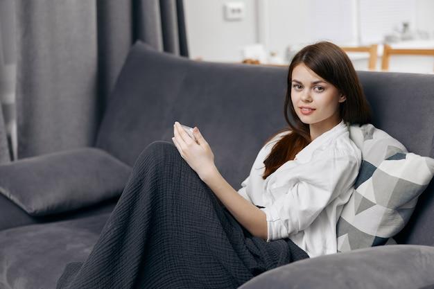Gelukkige vrouw die op bank met telefoon in handbinnenland rust