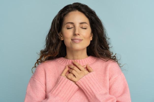 Gelukkige vrouw die op blauwe studioachtergrond wordt geïsoleerd, houd de handen op de borst en voel dankbaar.