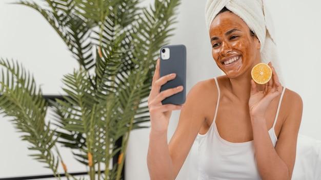 Gelukkige vrouw die op haar gezichtsmasker wacht om zijn effect te maken