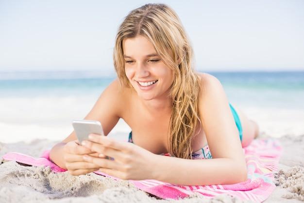 Gelukkige vrouw die op het strand ligt en mobiele telefoon met behulp van