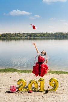 Gelukkige vrouw die op het strand springt met ballonnen 2019