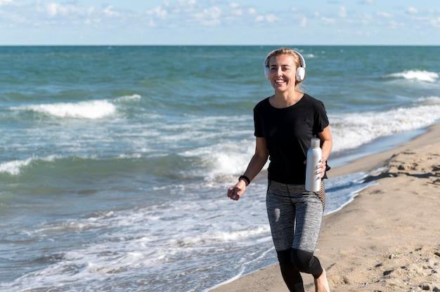 Gelukkige vrouw die op kust loopt