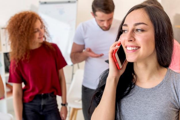 Gelukkige vrouw die op mobiele telefoon met haar vrienden spreekt