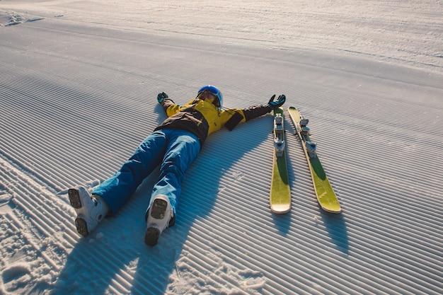 Gelukkige vrouw die op ochtendfluweel ligt met ski-kopieruimte