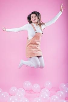 Gelukkige vrouw die op vloer met luchtballons springt