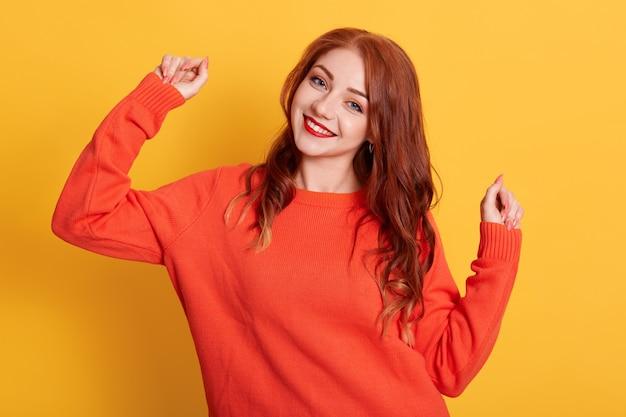 Gelukkige vrouw die oranje sweater draagt, die glimlachend camera met het opheffen van handen bekijkt, status geïsoleerd