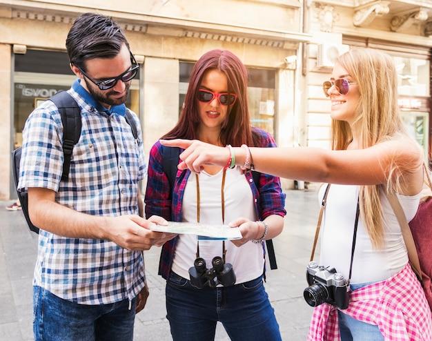 Gelukkige vrouw die richting toont aan haar vrienden die kaart houden