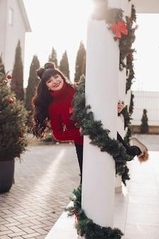Gelukkige vrouw die rode sweater draagt en van achter een witte kolom gluurt die met klatergoud wordt verfraaid