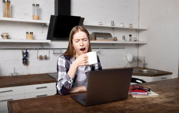 Gelukkige vrouw die 's ochtends thuis werkt. jong meisje gaapt. ze gebruikt haar laptop