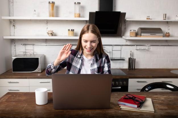 Gelukkige vrouw die 's ochtends thuis werkt. meisje dat koffie drinkt. ze gebruikt haar laptop