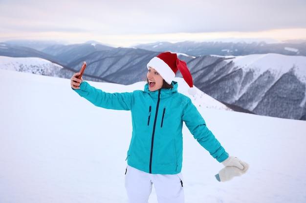 Gelukkige vrouw die selfie neemt in besneeuwde resort. winter vakantie