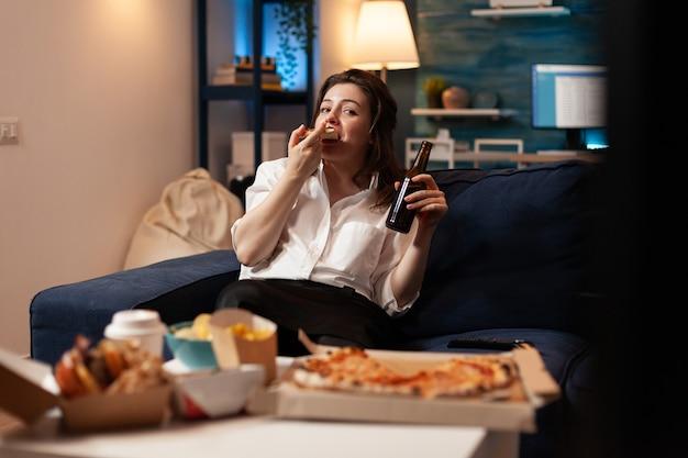 Gelukkige vrouw die smakelijke heerlijke pizza-plak eet ontspannen op de bank