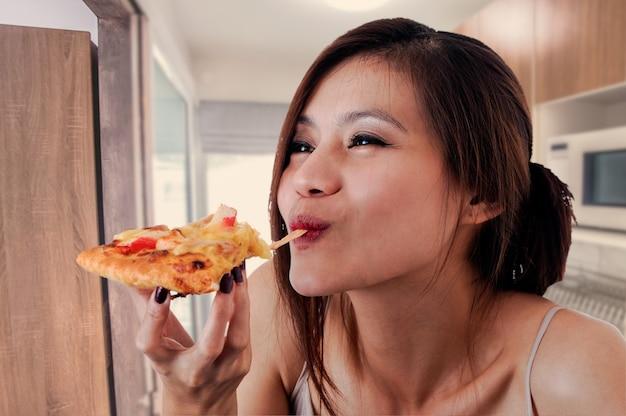 Gelukkige vrouw die smakelijke pizza eet.