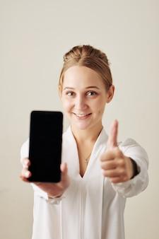 Gelukkige vrouw die smartphone toont