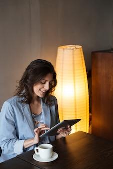Gelukkige vrouw die tabletcomputer met behulp van.