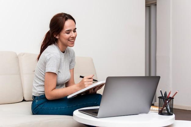 Gelukkige vrouw die terwijl het bekijken laptop werkt