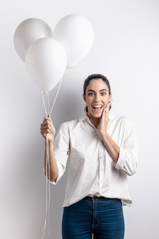Gelukkige vrouw die terwijl het houden van ballons stellen