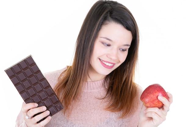 Gelukkige vrouw die tussen donkere chocolade en rood appelfruit kiezen over wit