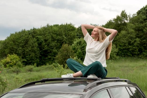 Gelukkige vrouw die van aard genieten terwijl bovenop auto