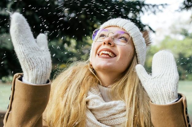 Gelukkige vrouw die van de sneeuwval geniet in het park in de winter