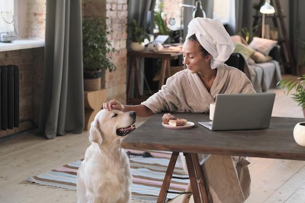 Gelukkige vrouw die van haar hond houdt tijdens het ontbijt aan tafel in de ochtend