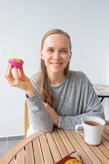 Gelukkige vrouw die van koffiepauze thuis geniet