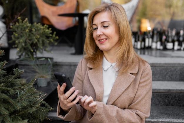 Gelukkige vrouw die van middelbare leeftijd haar telefoon controleert