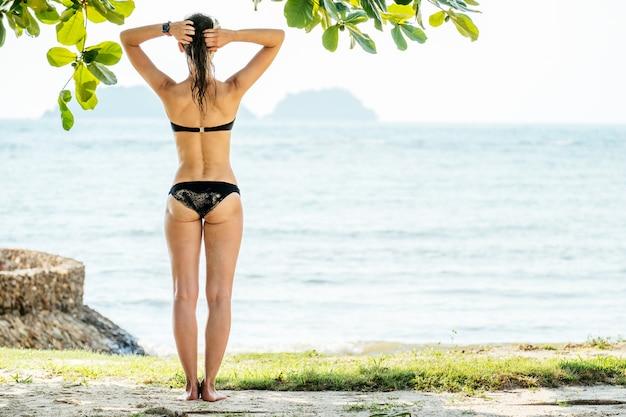 Gelukkige vrouw die van strand in de zomer geniet. mooi bikinimodel dat op reis ontspant
