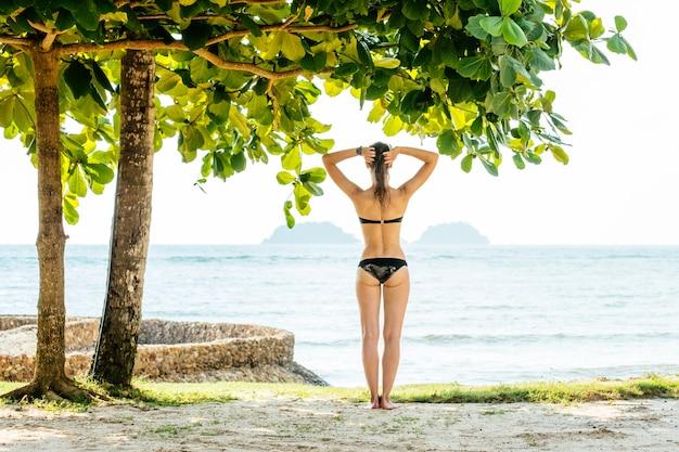 Gelukkige vrouw die van strand in de zomer geniet