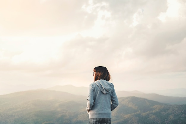 Gelukkige vrouw die van vrijheid bovenop berg met het concept van de zonsondergangontspanning genieten