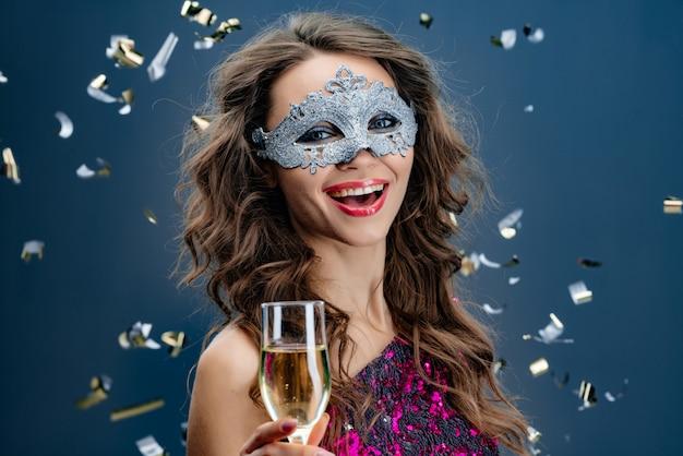 Gelukkige vrouw die venetiaans carnaval-masker dragen bij partij over vakantieachtergrond met klatergoud