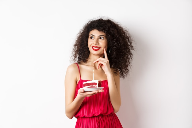 Gelukkige vrouw die verjaardag viert, cake houdt en wens doet, opzij dromerig kijkt, die zich in rode kleding op witte achtergrond bevindt. viering en vakantieconcept.