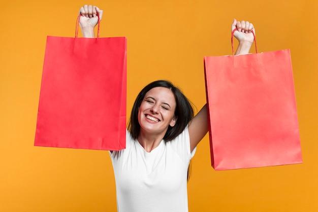 Gelukkige vrouw die verkoop het winkelen zakken steunt