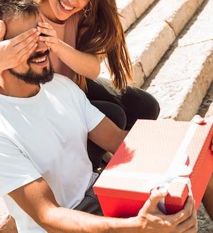 Gelukkige vrouw die verrassingsgift geeft aan haar vriend