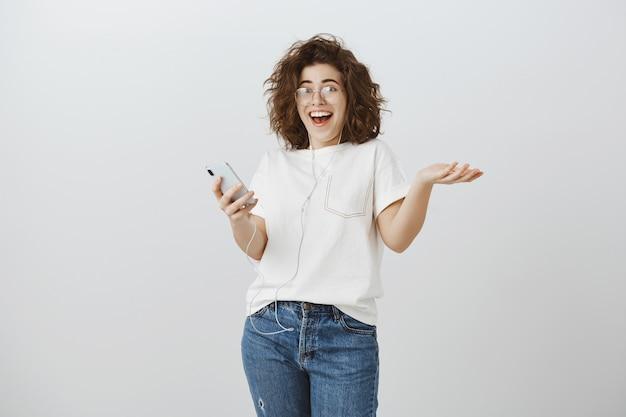 Gelukkige vrouw die verrast en opgewonden kijkt van groot nieuws, bericht leest op telefoon en zich verheugt