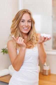 Gelukkige vrouw die vochtinbrengende crème op gezicht in de ochtend toepast
