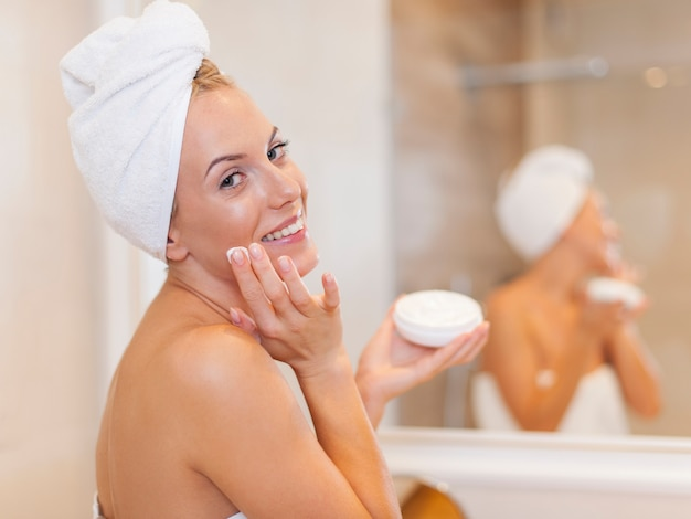 Gelukkige vrouw die vochtinbrengende crème op gezicht toepast na de douche