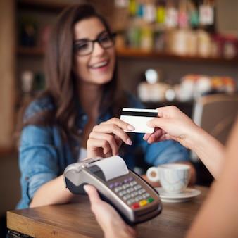 Gelukkige vrouw die voor koffie met creditcard betaalt